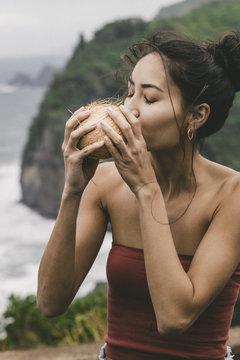 Woman drinking coconut water, Kailua Kona, Hawaii, USA