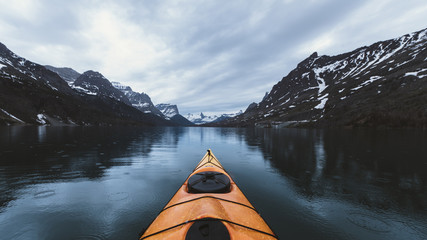 Kayak sailing on lake against mountains and cloudy sky at Glacier National Park during rainfall