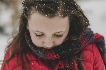 Close-up of girl wearing red warm clothing during snowfall