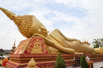 Large gilded Reclining Buddha statue at the Wat That Luang Tai Temple in Vientiane, Laos.