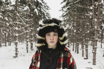 Portrait of confident teenage boy wearing warm clothing while standing in forest during snowfall