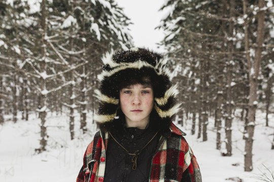 Winter portrait of  teenage boy wearing fur hat