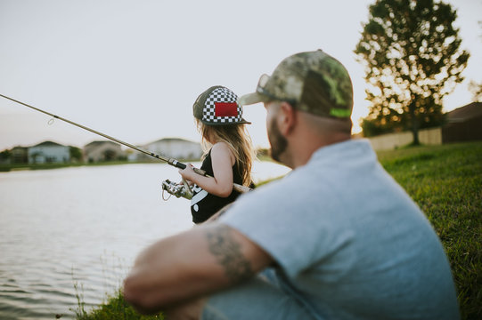 Side view of daughter fishing in river while father sitting on riverbank at park during sunset