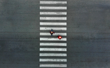 Aerial. Two pedestrians walk on a pedestrian crossing.