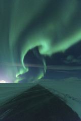 Scenic view of road amidst snow covered landscape against aurora borealis at night