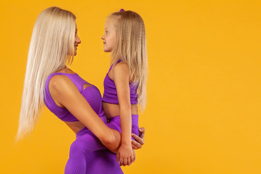 Mother's day concept. Fitness family look. Young mother athlete and daughter exercise together indoors.