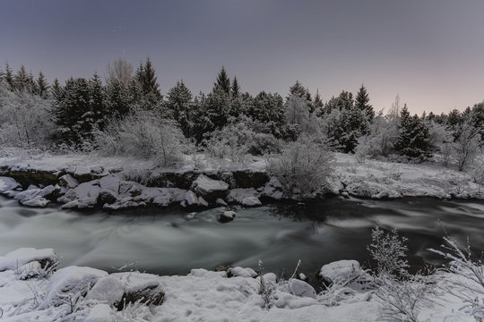 Scenic view of river amidst snow covered trees against clear sky at dusk