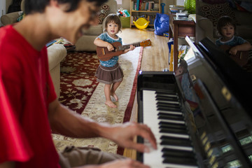 Father playing piano while daughter practicing guitar at home