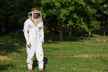 Beekeeper wearing white suit while walking on grassy field