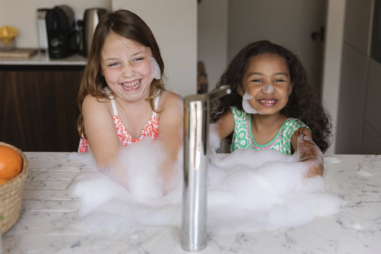 Two girls playing with soap suds in kitchen sink at home