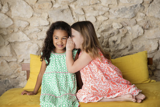 Girl whispering secret in friend's ear at home