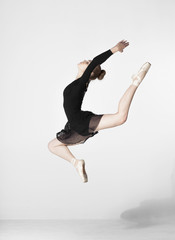 Full length of ballerina jumping while dancing against white background