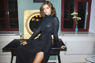 Portrait of confident young woman wearing black dress while sitting on table at home