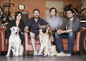 Portrait of coworkers with dogs sitting on armchairs in bike shop