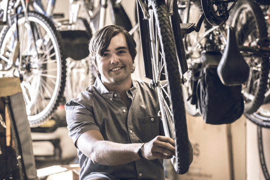 Portrait of owner repairing bicycle tire in workshop