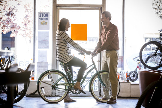 Owner looking at happy customer examining bicycle in store