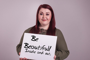 Be beautiful inside and out board held by young lady smiling