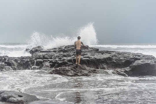 Man carrying surfboard while standing on rocks at beach against sky