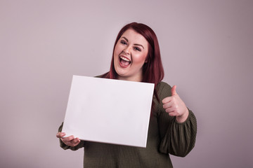 Young woman holding an empty white board giving a thumbs up excited facial  expression