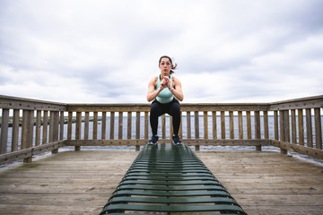 Confident woman jumping on bench against cloudy sky