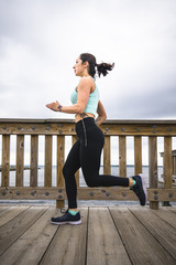 Side view of woman running on pier against cloudy sky