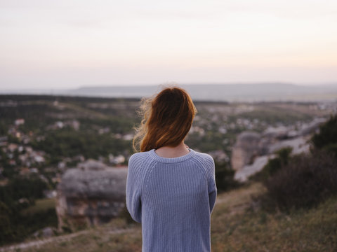 Rear view of woman looking at view while standing on mountain against sky during sunset