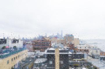 Buildings in city seen through wet glass window during rainy season