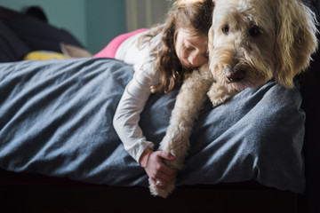 Girl and dog lying on bed at home