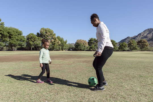 Mother and daughter playing soccer on field at park during sunny day