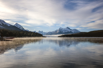 Scenic view of Maligne lake by snowcapped mountains against cloudy sky at Jasper National Park