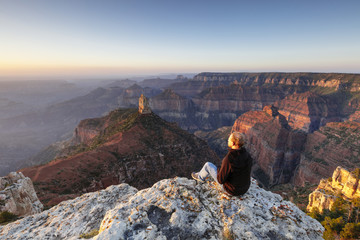 Rear view of male hiker looking at Grand Canyon National Park while sitting on Point Imperial against clear sky during sunset