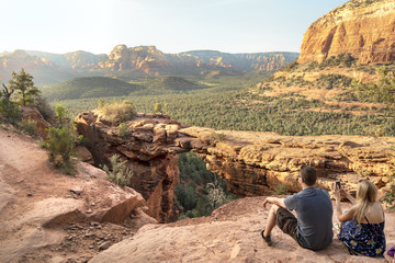 Rear view of tourists sitting on cliff by Devil's Bridge at desert