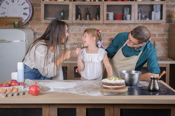Parents and daughter sing in the kitchen and cook dinner