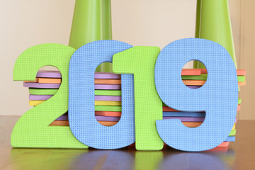 Close up number 2019 of green and blue flat foam children toy vertically standing on the table lay on stack colorful letters inside a room
