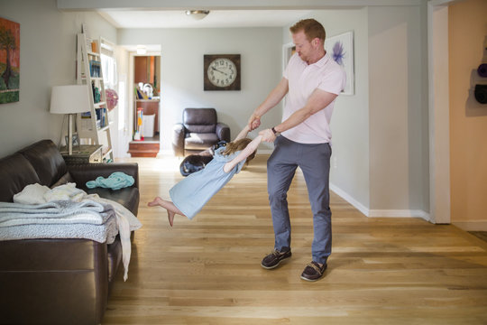Full length of father spinning daughter on hardwood floor in living room at home
