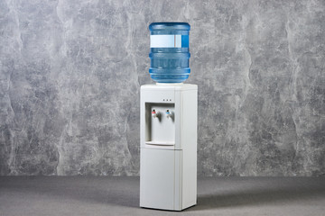White water cooler gallon in office against gray textured wall background. International Exhibition furniture elements in large warehouse interior.