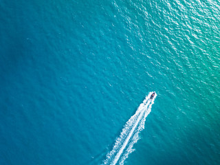 Bird's eye aerial top view of a boat cruising in crystal clear turquoise sea water Fotomurales