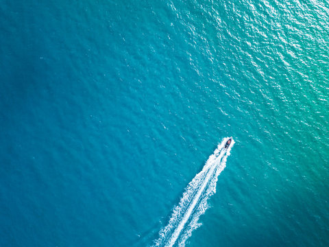 Bird's eye aerial top view of a boat cruising in crystal clear turquoise sea water