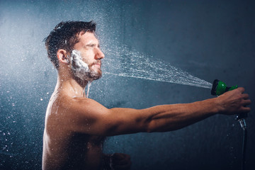 Headshot of a handsome bearded young man with eyes closed, holding a shower head and taking shower, with water splashes all over his face