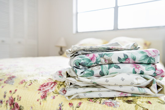 Stack of bedroom linen with floral, flower pattern on top of bed with quilt, quilted comforter, duvet, bright natural light from window, lamp, closet in background