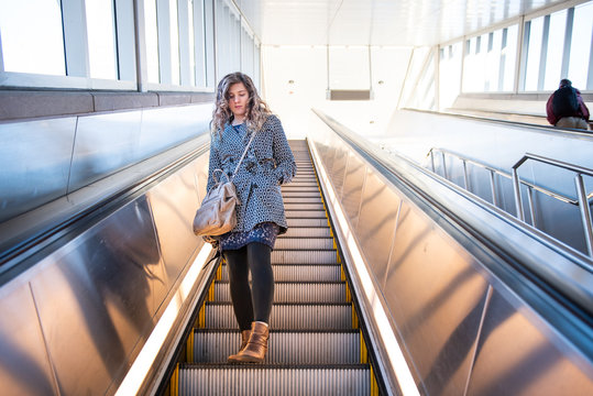 Low angle view, looking up of young woman standing on metro, subway, airport escalator going down with stairs, steps, bright light outside with people, man