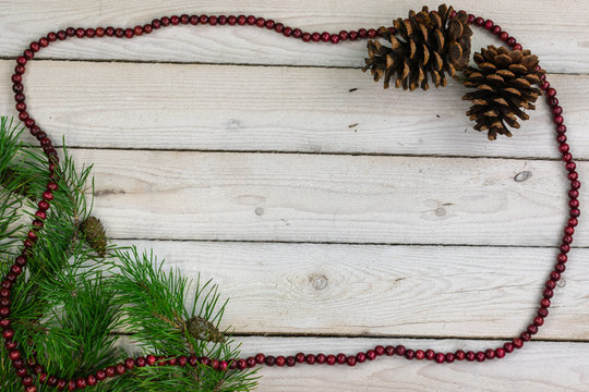 Scotch pine boughs and pine cones on whitewashed boards with a border of cranberry beads