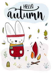 Cute rabbit is in fashionable clothes and is heated by the fire. Fall, autumn illustration. Vector