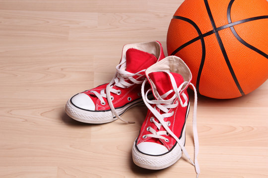 Basketball and red sneakers on the floor