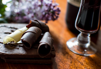 Dark Chocolate and White chocolate pieces on plate with glass of port red wine