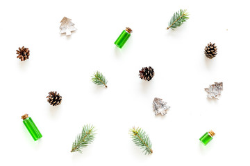 New Year pattern with pine sprigs, cones, spruce figure, fir oil on white background top view