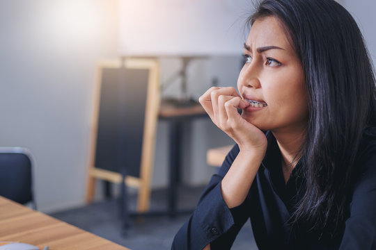 Nervous businesswoman biting her nails with worry emotion in office