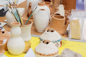 Ceramic tableware and brushes stand on a table for painting in a pottery workshop