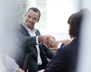 smiling businessman shaking hands with a business partner