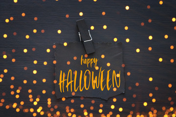 Halloween holiday minimal top view image of letter with text HAPPY HALLOWEEN over wooden background. Card and invitation concept.